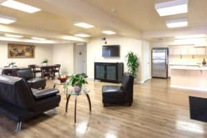 Kitchen, sitting area with couch and chairs and tables, television